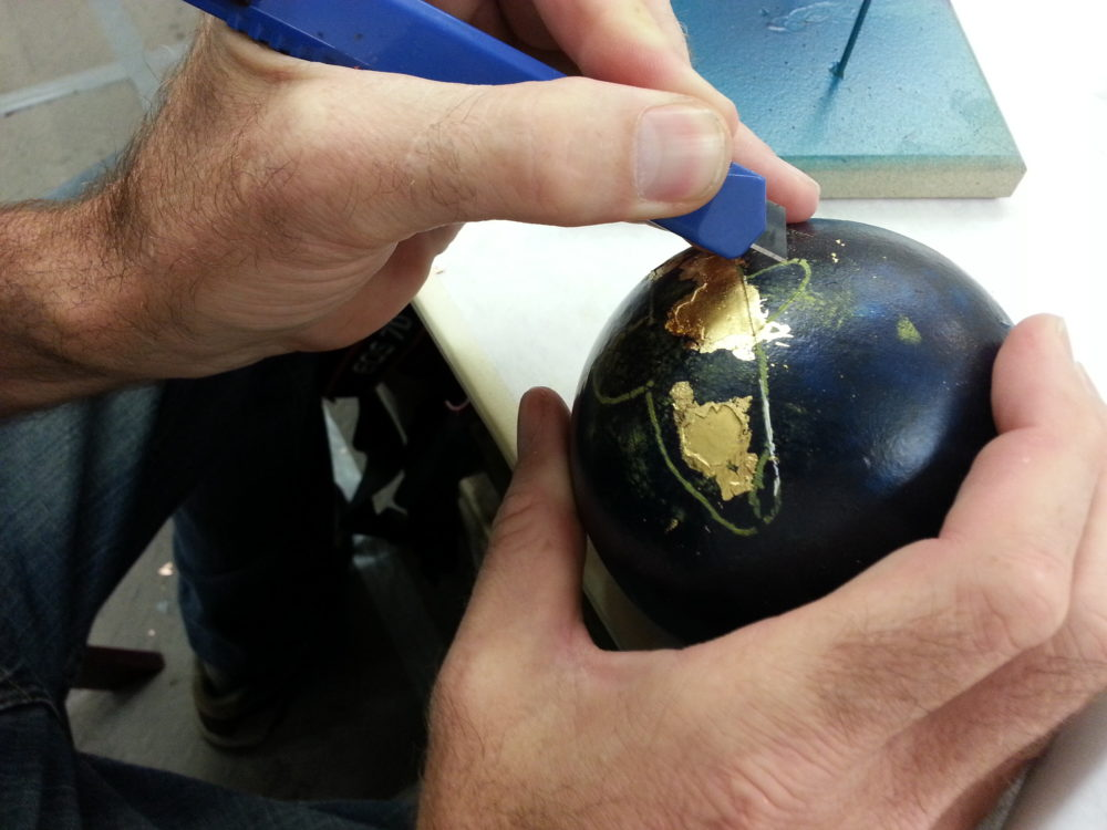 Student working on applying metal leaf to a sphere.