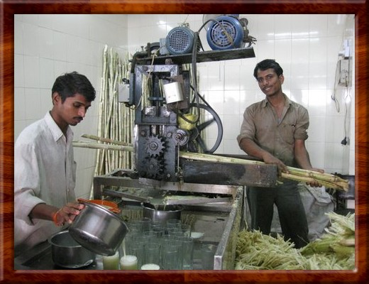 046 Workers making juice crushed from raw sugar cane stock harvested fresh each morning in Pune, India