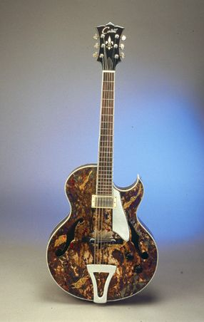 "This guitar was built by Tom Cerletti. This Collaborative project ""Cerletti / Marks"", 17″ archtop model was built in 1999 for guitarist Steve Kimock, the guitar is made of German spruce and rock maple. The neck is Cuban cedar. The David J. Marks finish is of copper, silver and gold leaf; the chemical is patina, with Japan paint and lacquer."
