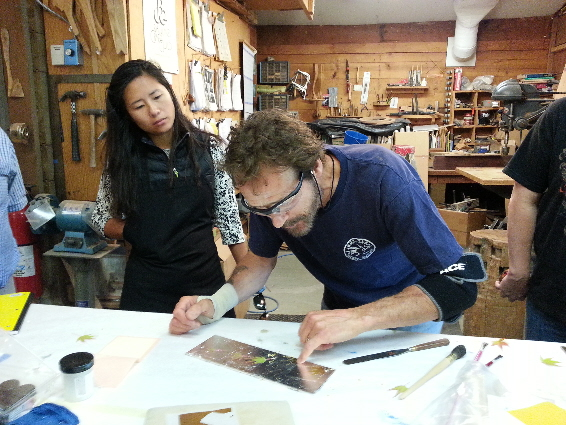 David demonstrating application of gold leaf to sample board.